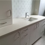 White Bathroom Countertop with Eased Edge Profile and Undermounted Square Sink. Has White Backsplash and White cabinets